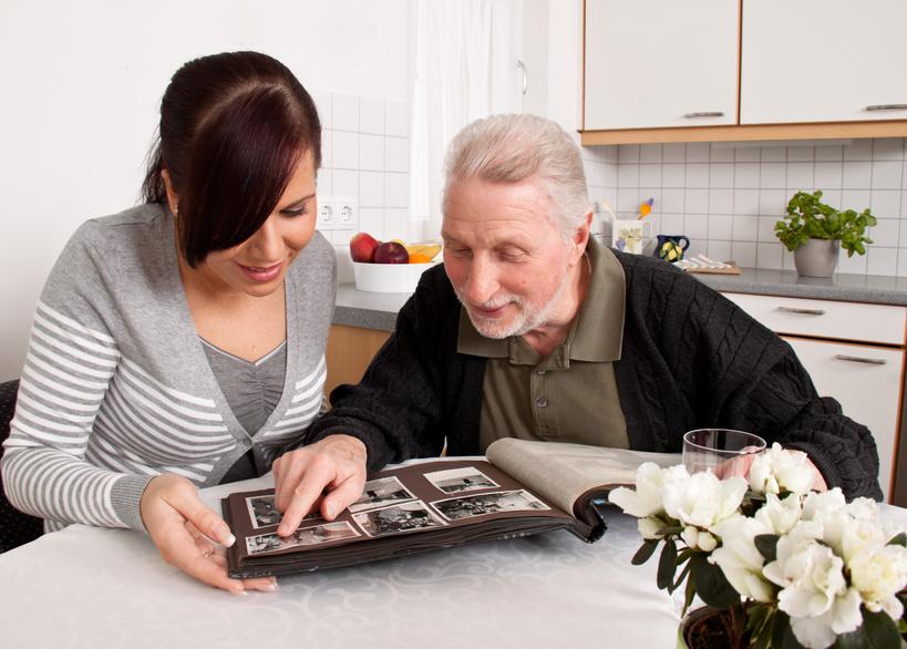 Frau schaut mit Senioren ein Fotoalbum an